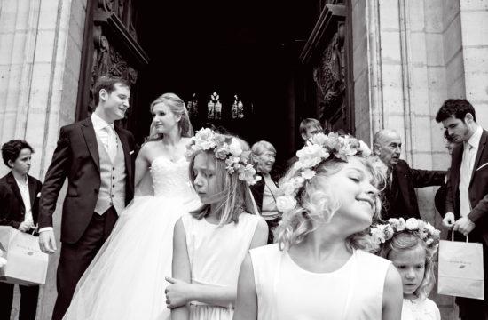 scène de mariage à la sortie d'une église. Trois enfants de coeur sont au premier plan. Les mariés et des invités sont en arrière plan