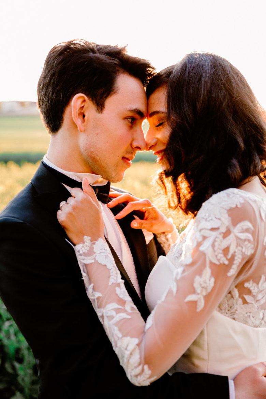 des mariés face à face s'enlacent dans une lumière dorée