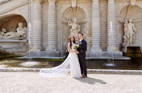 des mariés l'un à côté de l'autre au milieu d'une fontaine