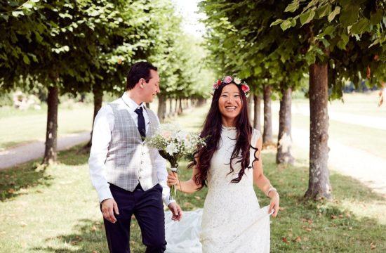 des mariés courent dans une allée d'arbres