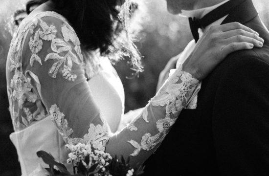 un couple de mariée se tiennent face à face. On voit un gros plan sur la robe de la mariée, elle tient son mari par les épaules