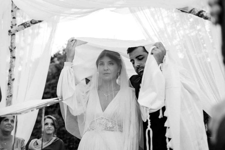les mariés se recueillent sous un morceau de tissus